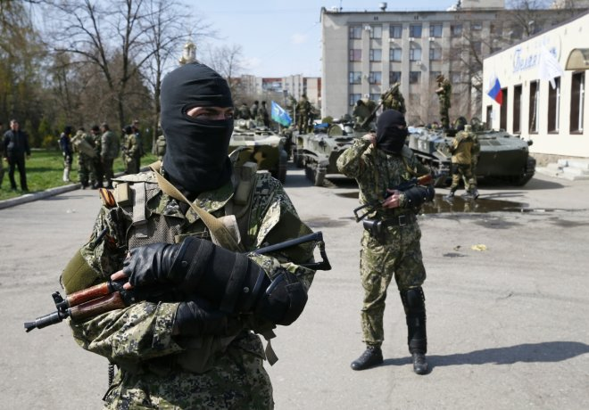 Armed men, wearing black and orange ribbons of St. George - a symbol widely associated with pro-Russian protests in Ukraine, stand guard hear armoured personnel carriers in Slaviansk