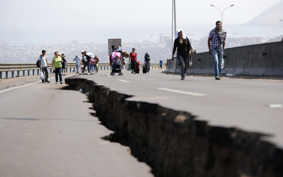 People walk next to a crack along a damaged road leading to Alto Hospicio commune, after a series of aftershocks, in the northern port of Iquique April 3