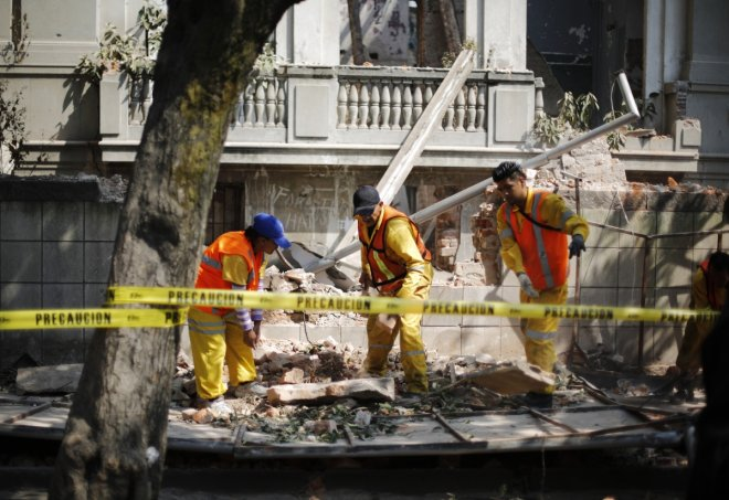 City workers remove the rubble of a wall that collapsed in an earthquake in Mexico City April 18