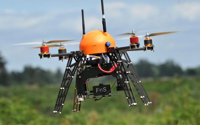 Unmanned flying drone flies across a farm