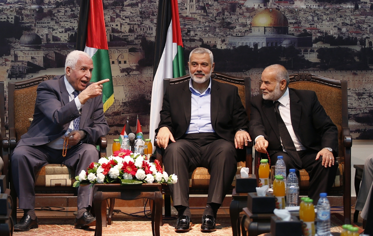 Azzam Al-Ahmed (L), a senior Fatah official and head of the Hamas government Ismail Haniyeh (C) and deputy speaker of Palestinian Parliament Ahmed Bahar attend a meeting in Gaza City