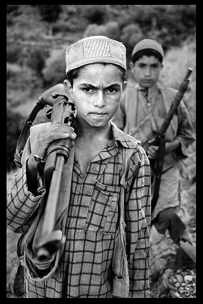 A young boy stands with his firearm, 1979