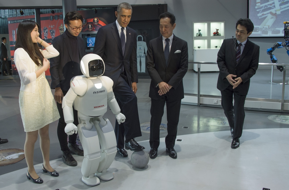 President Barack Obama plays football with Honda's humanoid robot ASIMO on a state visit to Japan