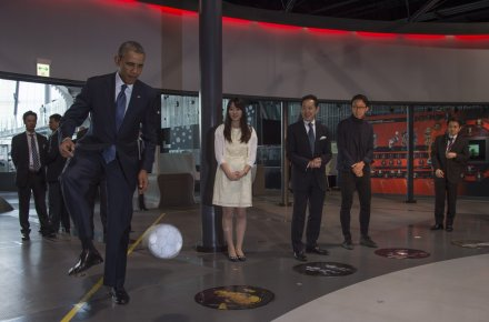 President Obama deftly stops and kicks the football back to the Honda robot ASIMO