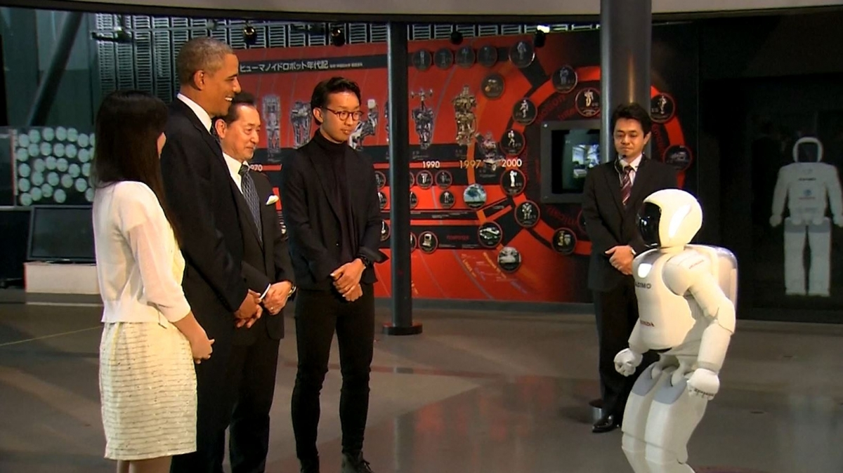 President Obama plays football with a humanoid robot while touring Japan
