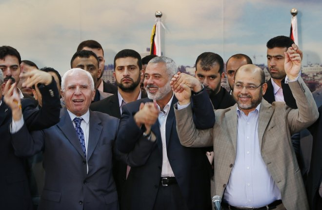 Senior Fatah official Azzam Al-Ahmed (L), head of the Hamas government Ismail Haniyeh (C) and senior Hamas leader Moussa Abu Marzouq hold their hands after announcing a reconciliation agreement in Gaza City