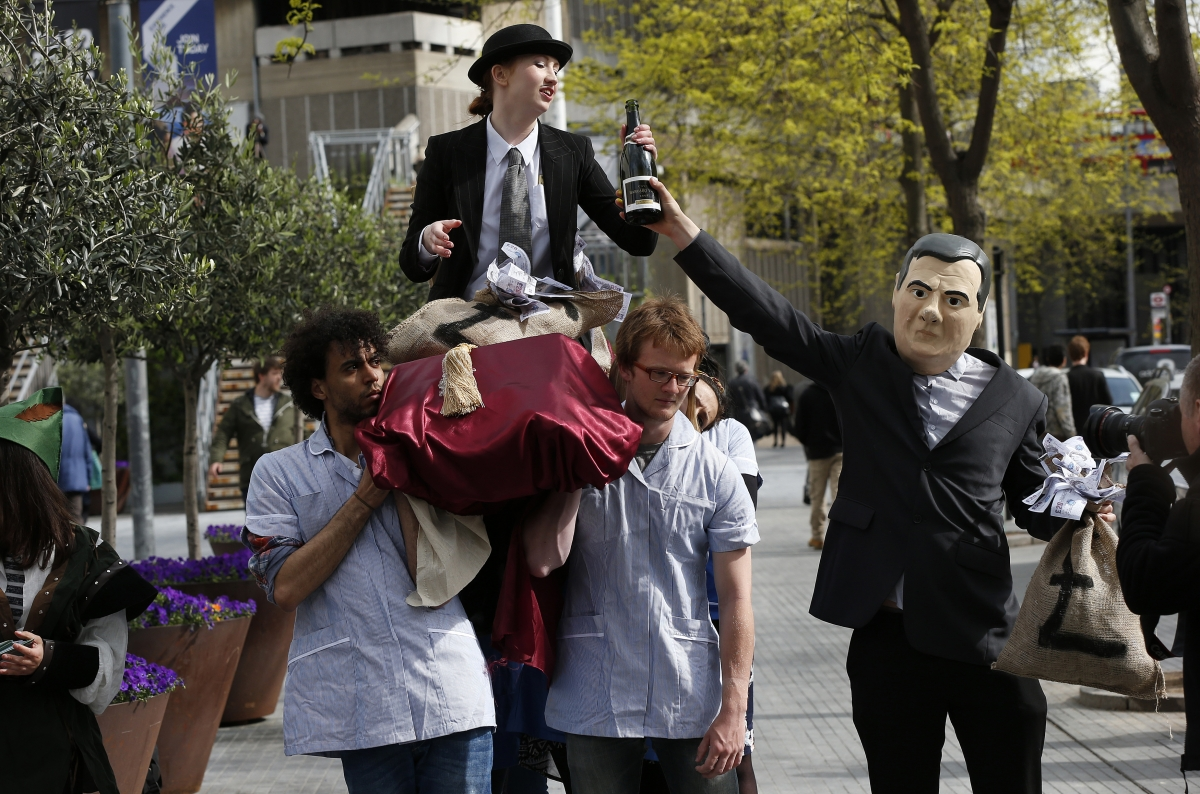 A demonstrator dressed as Britain's Chancellor of the Exchequer George Osborne hands a bottle of champagne to a fellow demonstrator dressed as a banker sitting aloft NHS workers, during a protest outside the Barclays AGM in central London April 24, 2014.