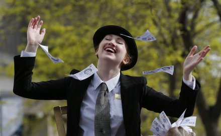 A demonstrator dressed as a banker throws away imitation bank notes during a protest outside the Barclays AGM in central London April 24, 2014.
