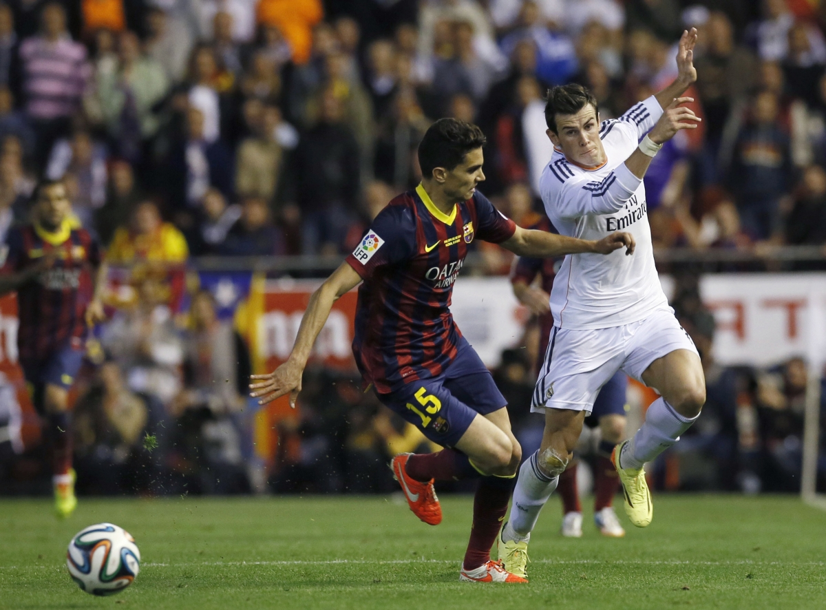 Barcelona\'s Marc Bartra (L) battles for the ball against Real Madrid\'s Gareth Bale before Bale scored his goal during their King\'s Cup final soccer match at Mestalla stadium in Valencia April 16, 2014.