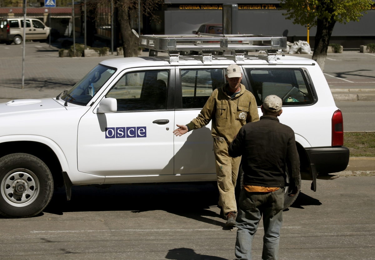 Municipal workers take a photo at an Organization for Security and Cooperation in Europe (OSCE) car near the seized office of the SBU state security service in Luhansk, eastern Ukraine