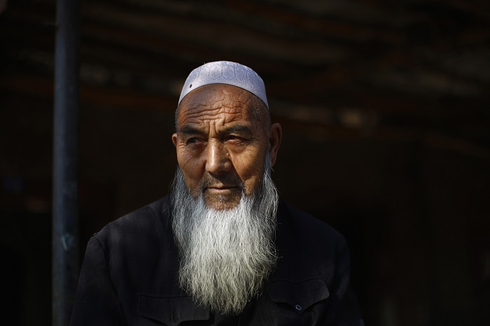 An ethnic Uighur man sits outside his house near a busy market in Turpan, Xinjiang province.