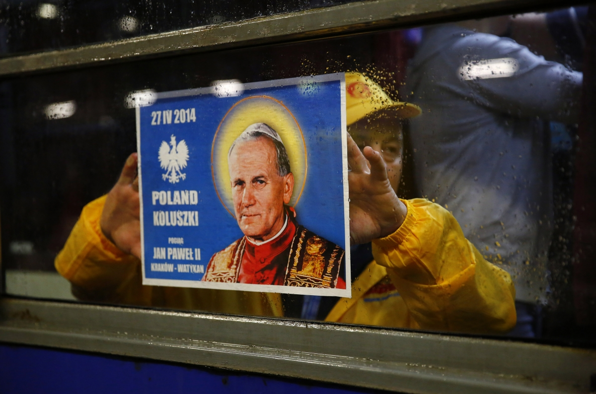 A Polish pilgrim holds up a poster as he travels to the Vatican to witness the canonisations of Pope John XXIII and Pope John Paul II