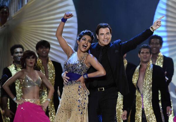 Priyanka Chopra on stage with John Travolta during IIFA 2014