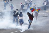 An anti-government protester wields the Venezuelan flag and kicks back a gas canister to police during anti-government demonstrations.