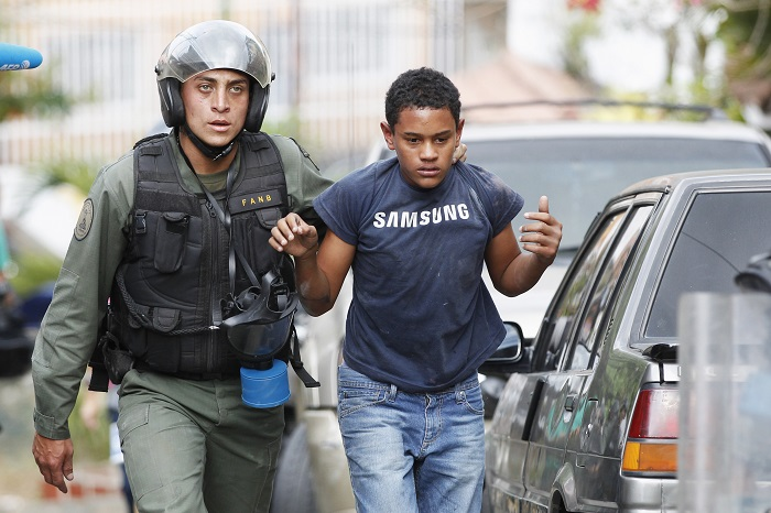 A young protester is detained by police during protests against education reforms in Venezuela.