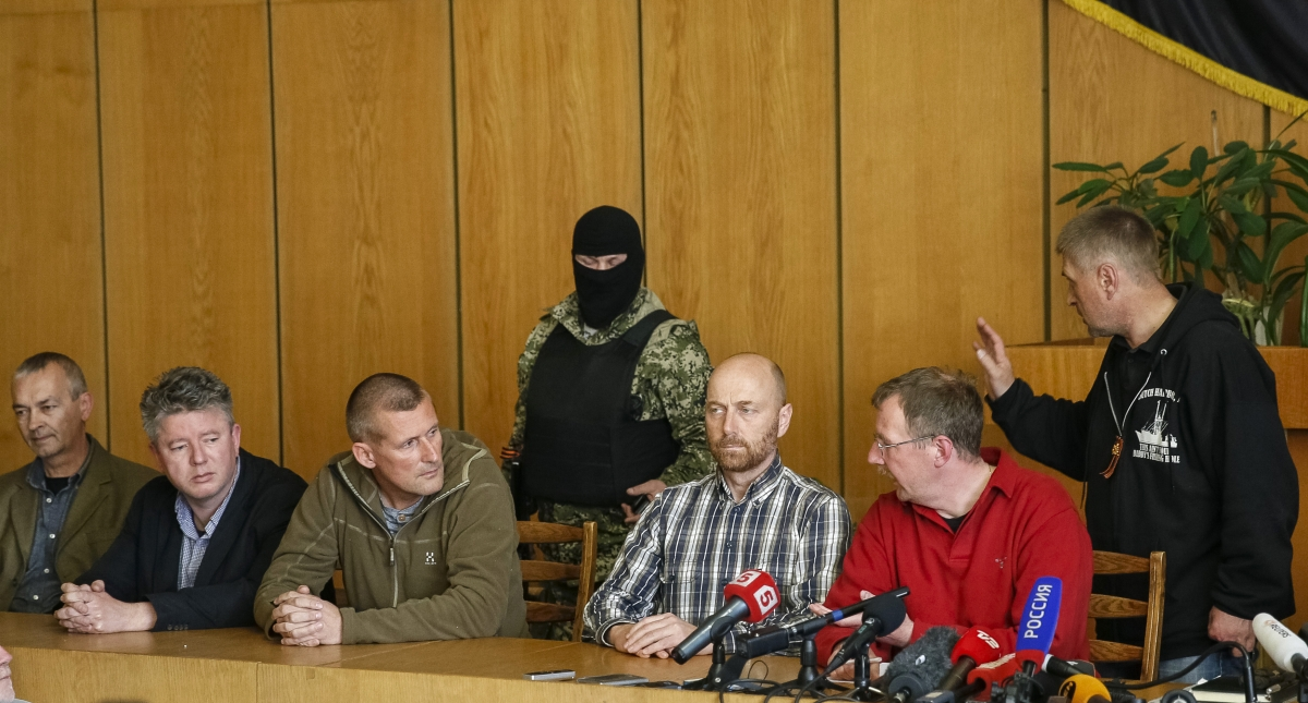 Vyacheslav Ponomaryov (R), separatist de facto mayor of Slaviansk, and detained international observers take part in a meeting with journalists in the eastern Ukrainian city of Slaviansk