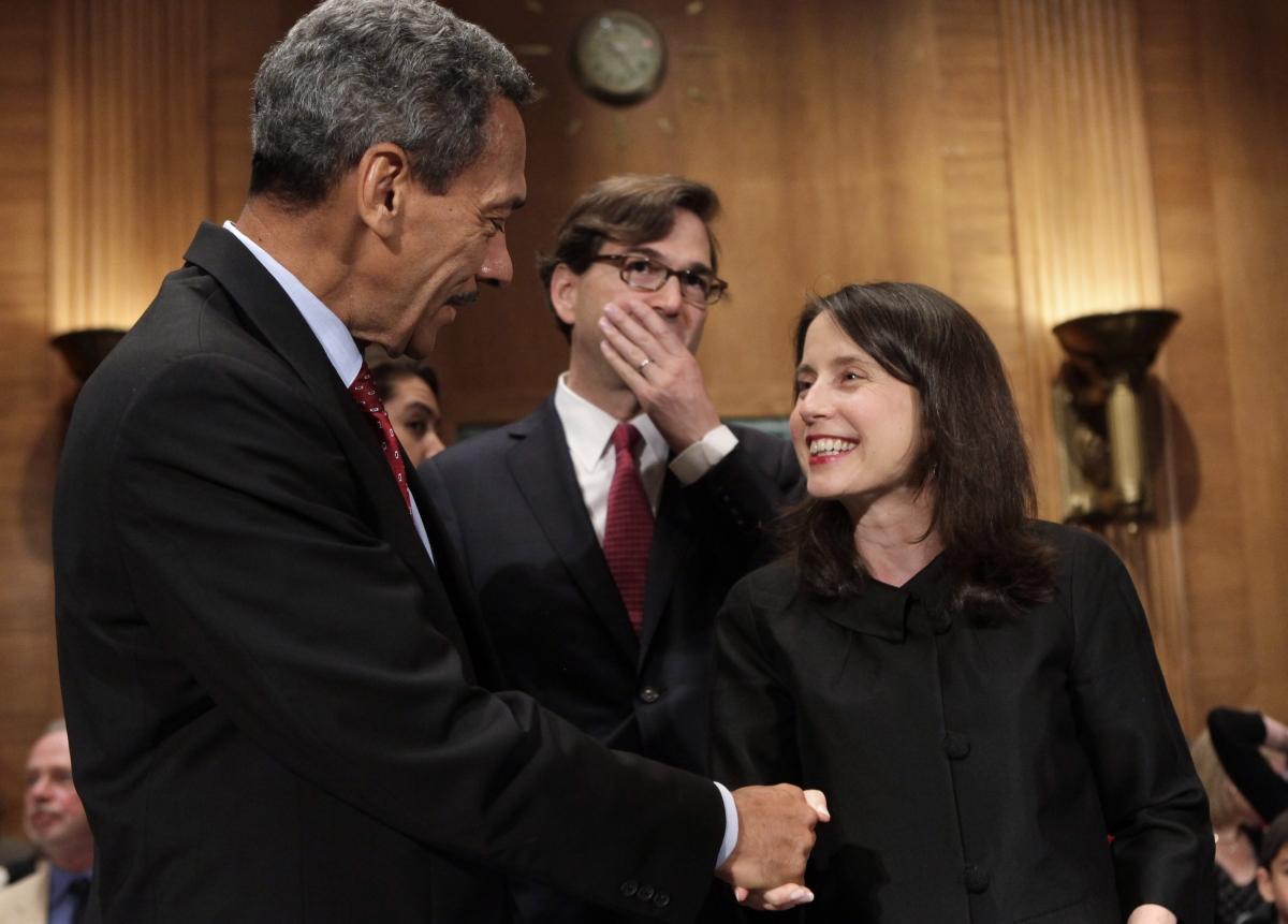 Representative Mel Watt (L), nominee to be the regulator of mortgage finance firms Fannie Mae and Freddie Mac, shakes hands with Kara Stein