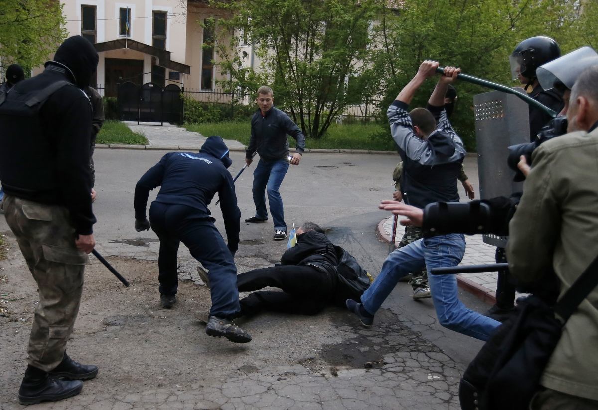 EU Slaps Sanctions on 15 Russian Politicians, Separatist Leaders and Military Chiefs: pro-Russian protesters attack a pro-Ukranian protester during a pro-Ukraine rally in the eastern city of Donetsk April 28, 2014.