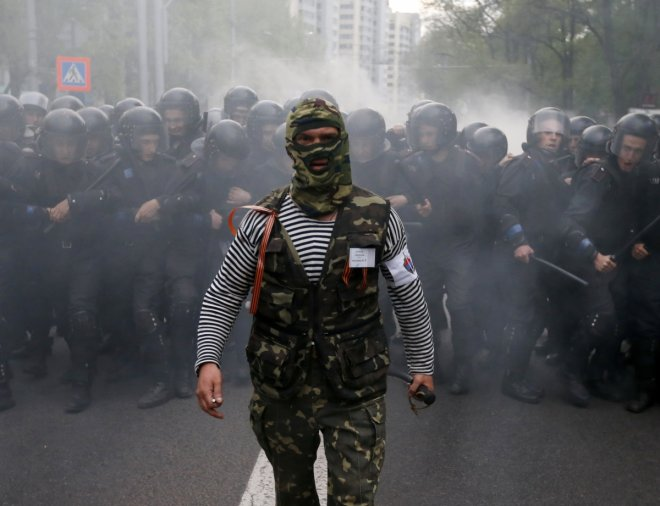 A pro-Russian activist walks in front of Ukrainian riot police during a pro-Ukrainian rally in the eastern city of Donetsk April 28