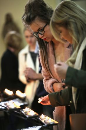 Mourners light candles at a mass for Anne Maguire at Corpus Christi Church, after the teacher was stabbed to death during class in Leeds