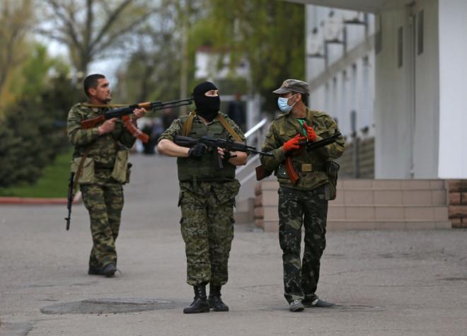 Pro-Russian armed men walk near the local police headquarters in Luhansk, eastern Ukraine
