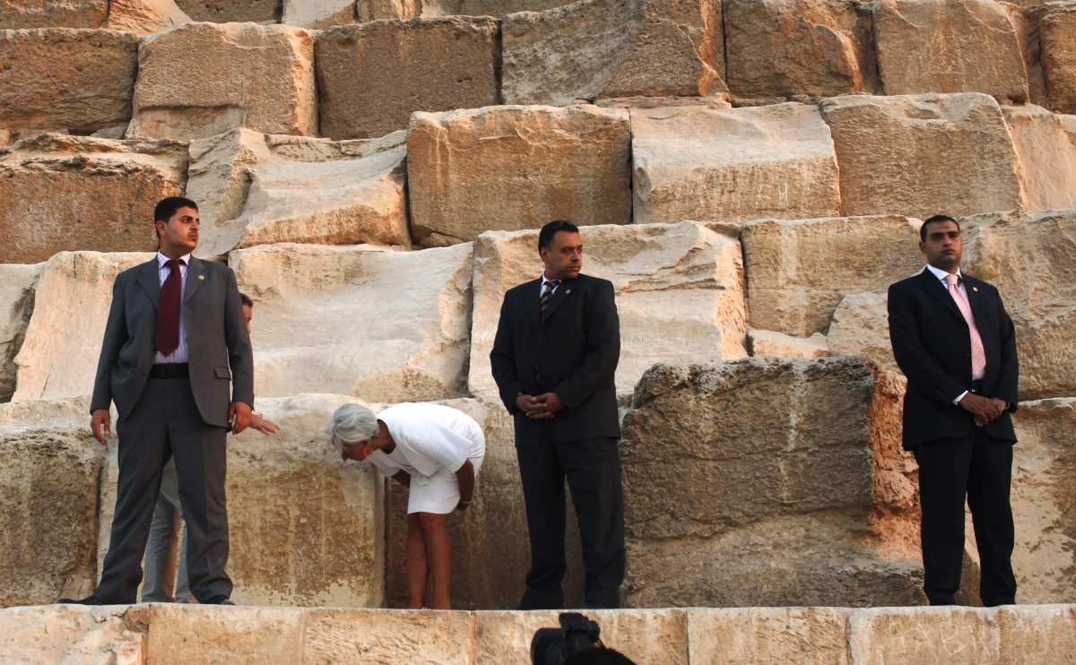International Monetary Fund (IMF) Managing Director Christine Lagarde (2nd L) checks some pyramid stones next to security guards