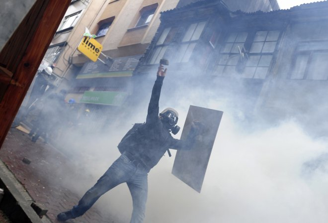 A protester throws stone at riot police during a May Day demonstration in Istanbul