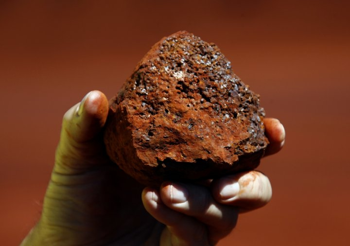 A miner holds a lump of iron ore