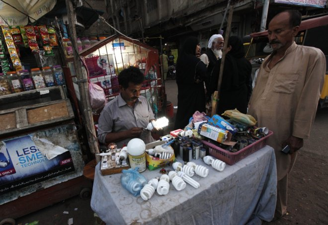 Man checks lightbulb in Karachi slum