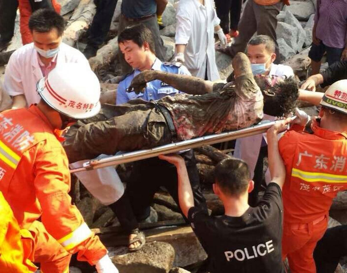Rescue workers carry an injured man after a bridge collapsed during construction in Maoming, Guangdong province