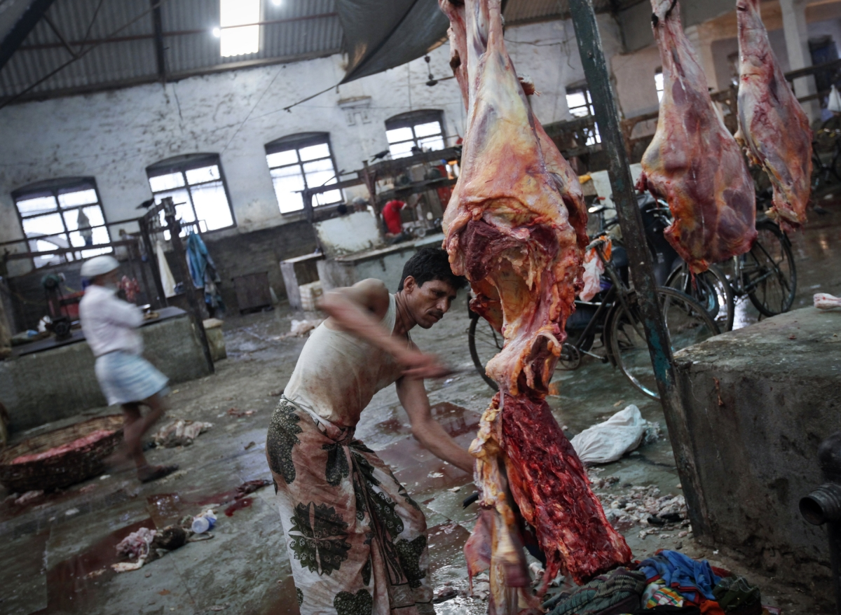 A butcher cuts up portions of beef for sale in an abattoir at a wholesale market in Mumbai