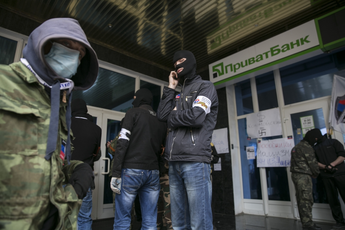 Masked pro-Russian activists stand outside a branch of Ukraine's Privatbank during a protest in Donetsk, eastern Ukraine