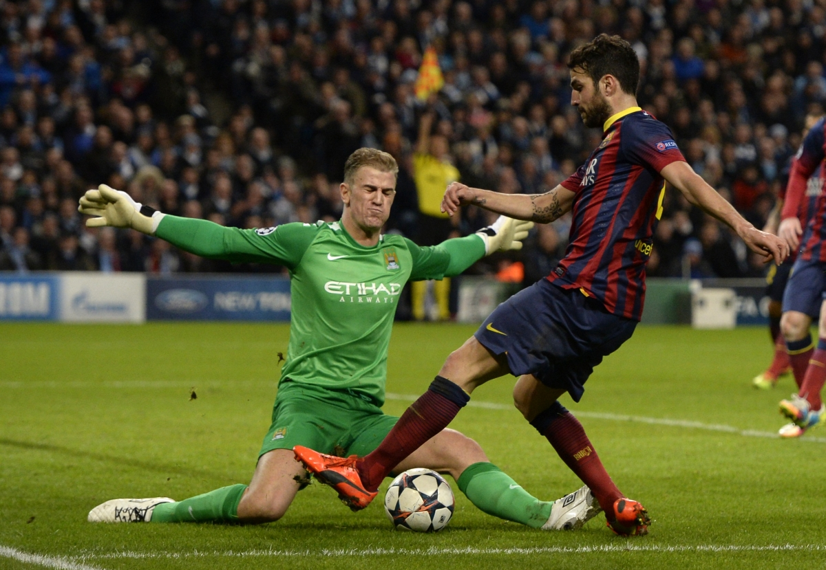 Manchester City's goalkeeper Joe Hart (L) blocks Barcelona's Cesc Fabregas during their Champions League round of 16 first leg soccer match at the Etihad Stadium in Manchester, northern England February 18, 2014.
