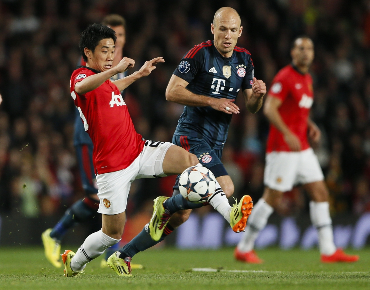 Manchester United's Shinji Kagawa (L) fights for the ball with Bayern Munich's Arjen Robben during their Champions League quarter-final first leg soccer match at Old Trafford in Manchester, April 1, 2014.