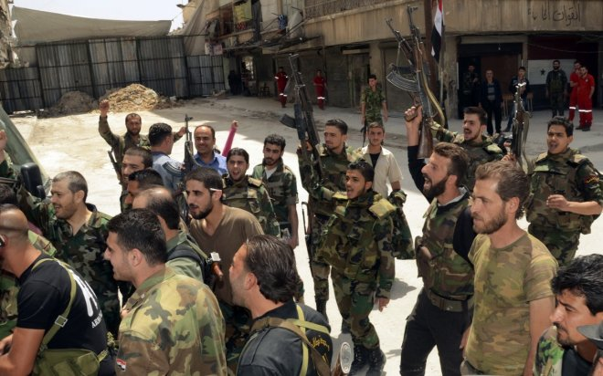 Forces loyal to Syria's President Bashar al-Assad cheer upon the release of their comrades by rebels in Aleppo's Bustan al-Qasr