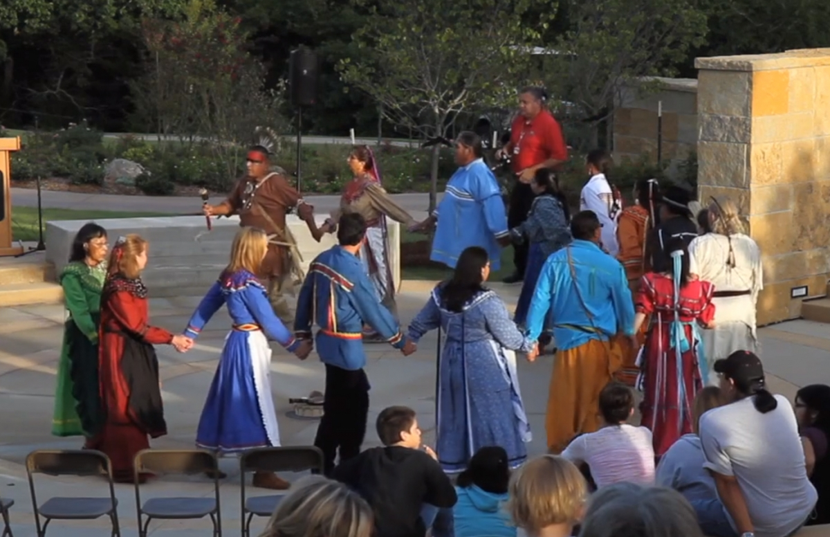 Chickasaw tribe members performing a stomp dance at the Chickasaw Cultural Center