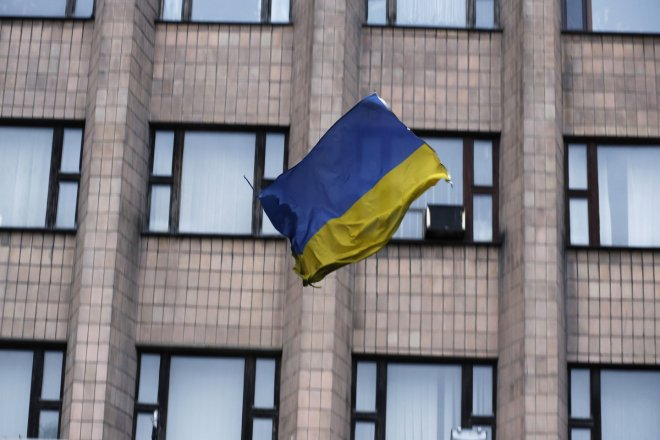 A Ukranian flag falls after it was thrown by pro-Russia protesters from the top of the district council building in Donetsk, eastern Ukraine