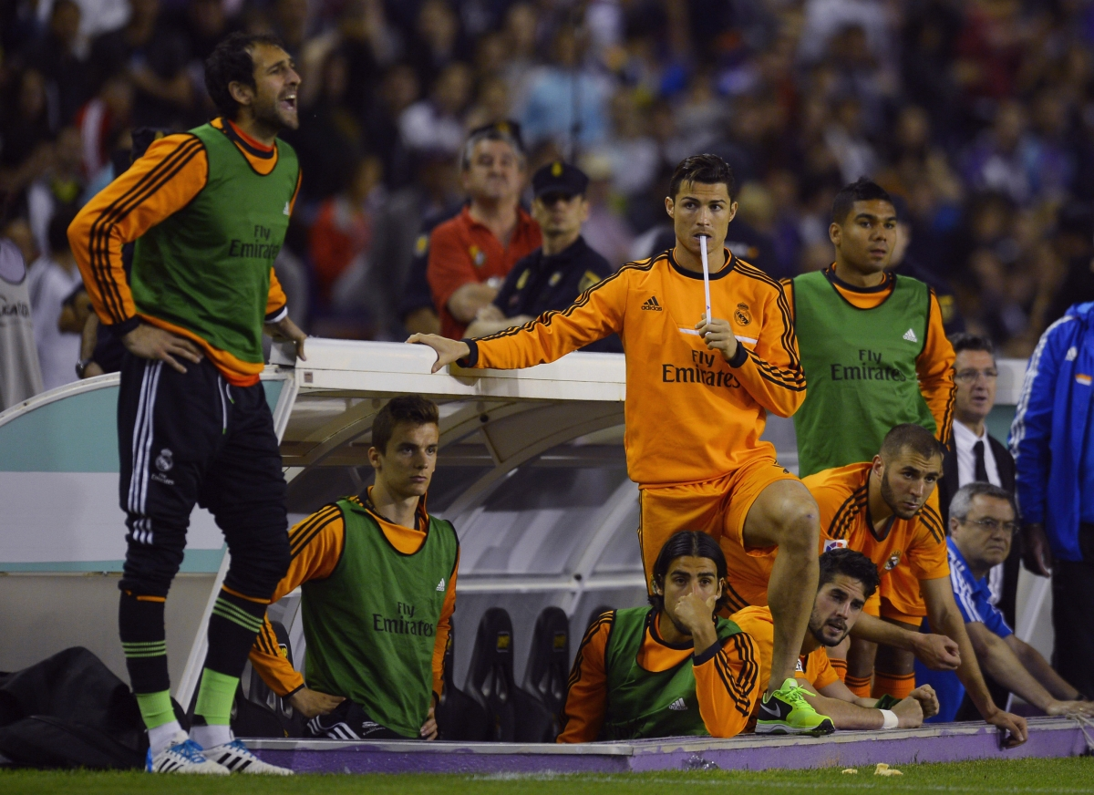 Real Madrid's Cristiano Ronaldo (C) and teammates watch their Spanish First Division soccer match against Valladolid from the bench, at Zorrilla Stadium in Valladolid May 7, 2014.