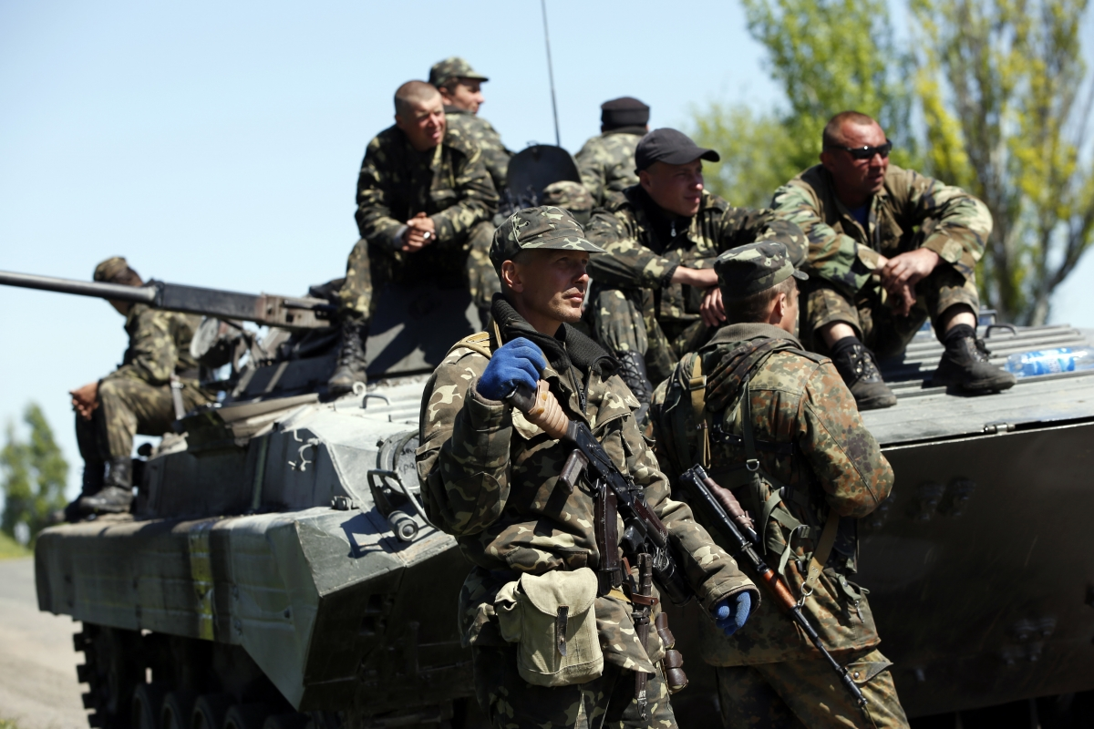Ukrainian soldiers stand guard beside an armoured personnel carrier at a checkpoint in Mariupol,