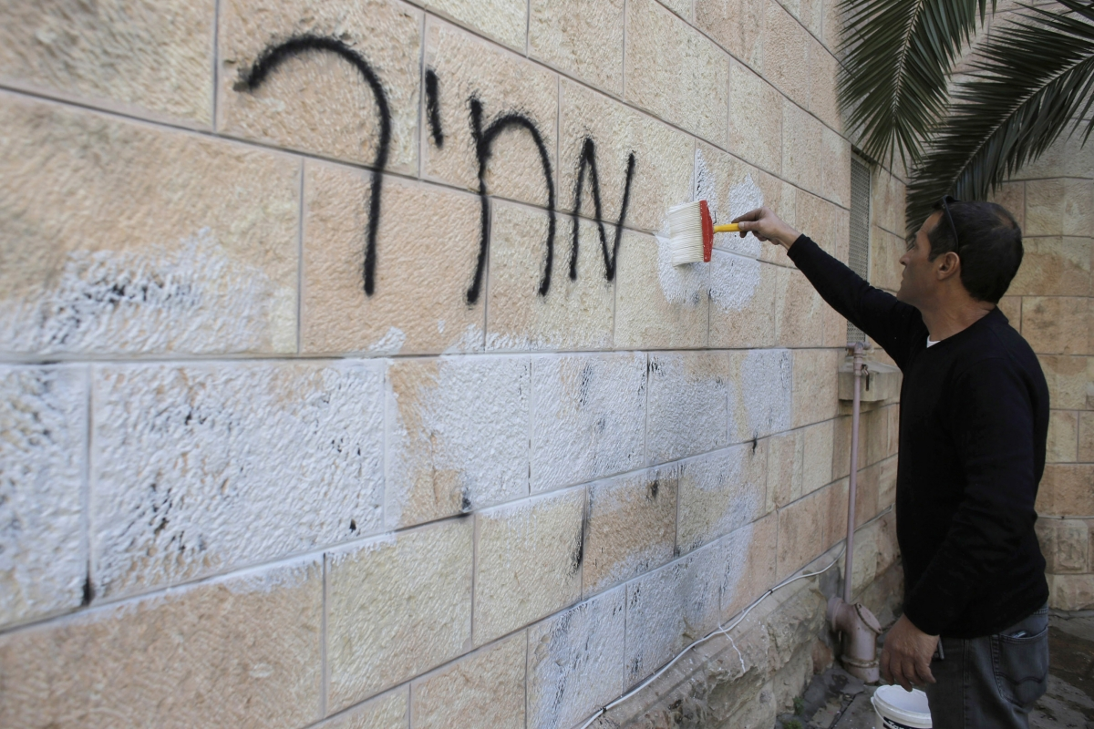 A municipality worker paints over graffiti daubed in Hebrew on a wall of the Romanian Orthodox Church in Jerusalem