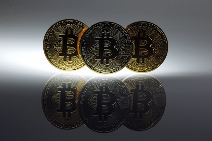 Mock Bitcoins are displayed on a table in an illustration picture