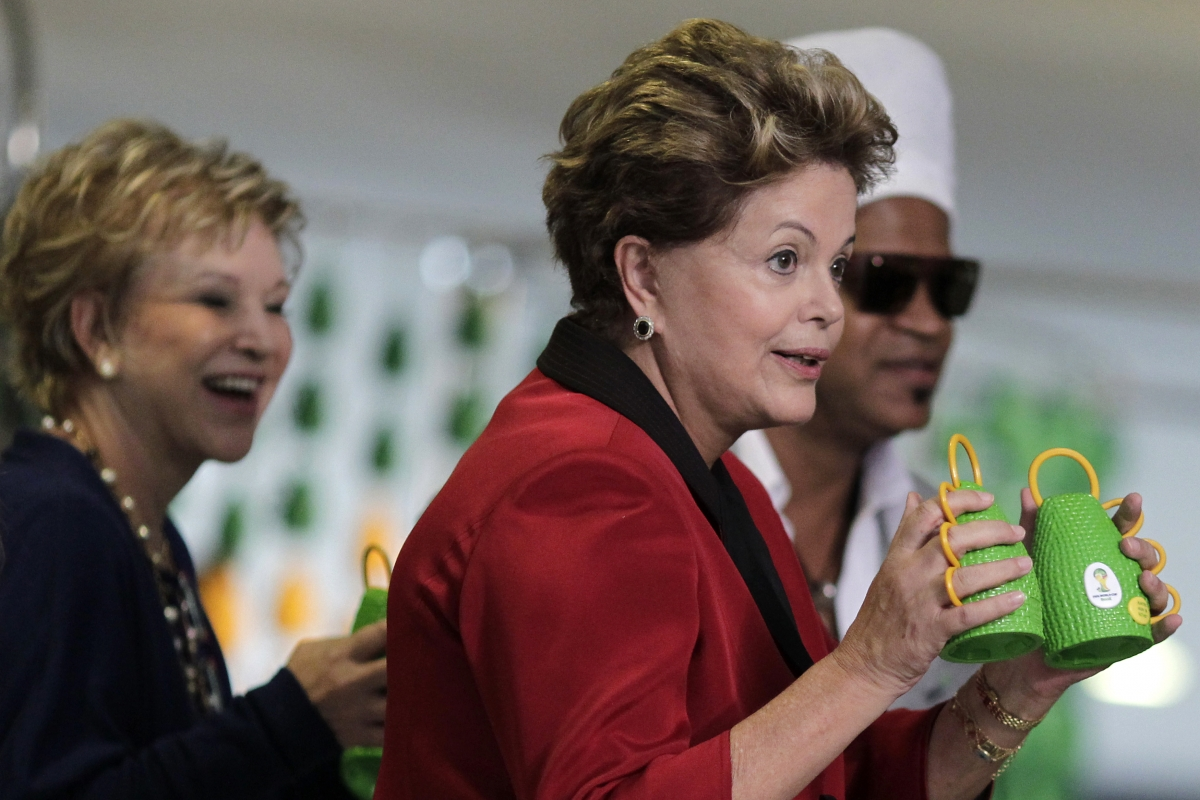 Brazil's President Dilma Rousseff holds the Caxirola, musical instrument to be used at the 2014 Brazil World Cup