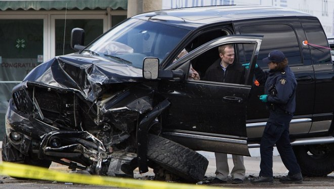 Royal Canadian Mounted Police officers inspect a smashed up truck involved in the shooting incident in St Paul, Alberta.