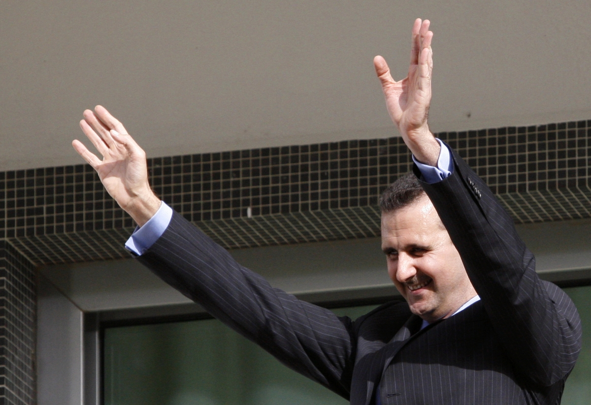 Bashar al-Assad waves to supporters from the balcony of the presidential palace in Damascus.