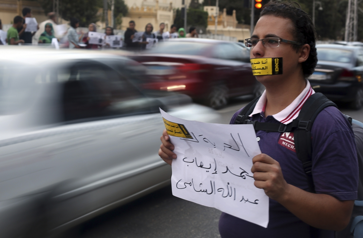 A demonstrator looks on with a sign reading