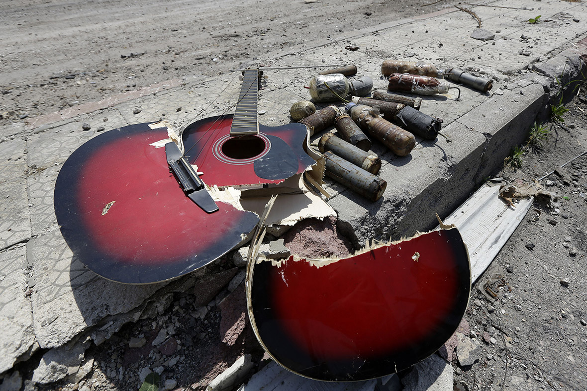A broken guitar lies  on the street  next to handmade grenades the Old City of Homs