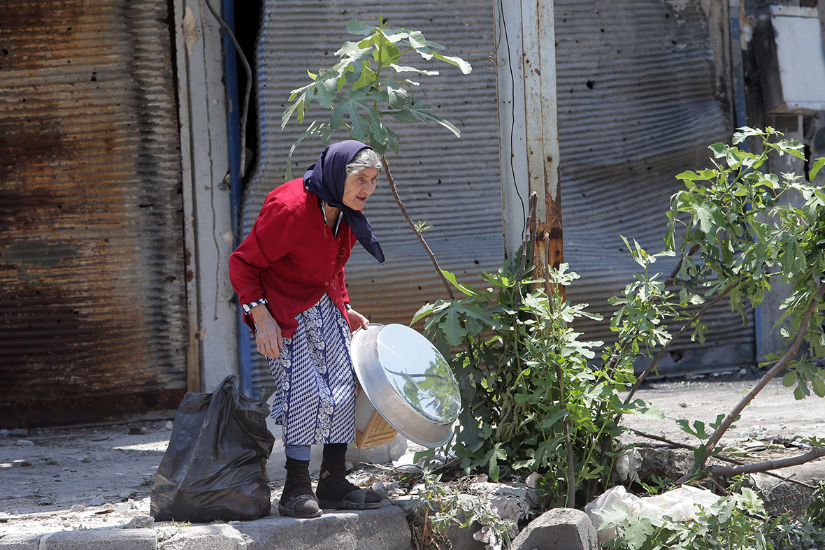 A woman retrieves belongings from her home in the Old City