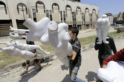 Syrian children carry shop mannequins in a destroyed neighbourhood of the Old City of Homs