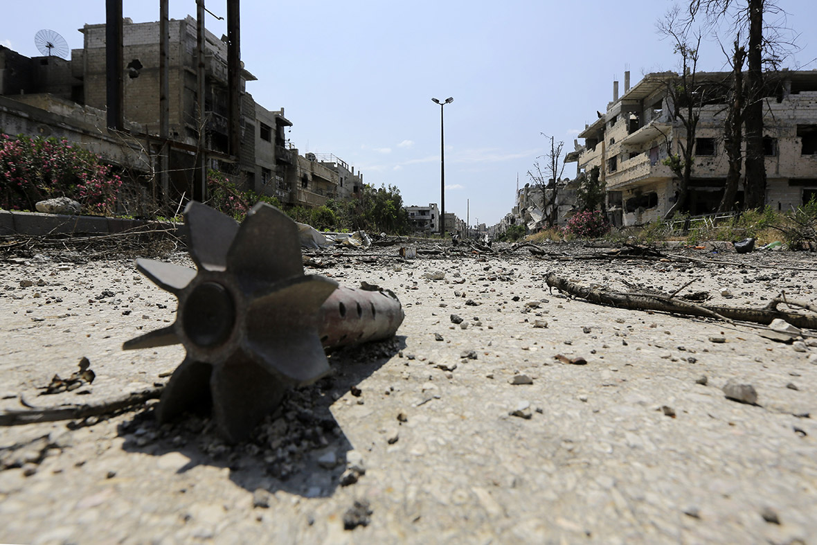 A mortar round is seen on a road in a destroyed neighbourhood of the Old City