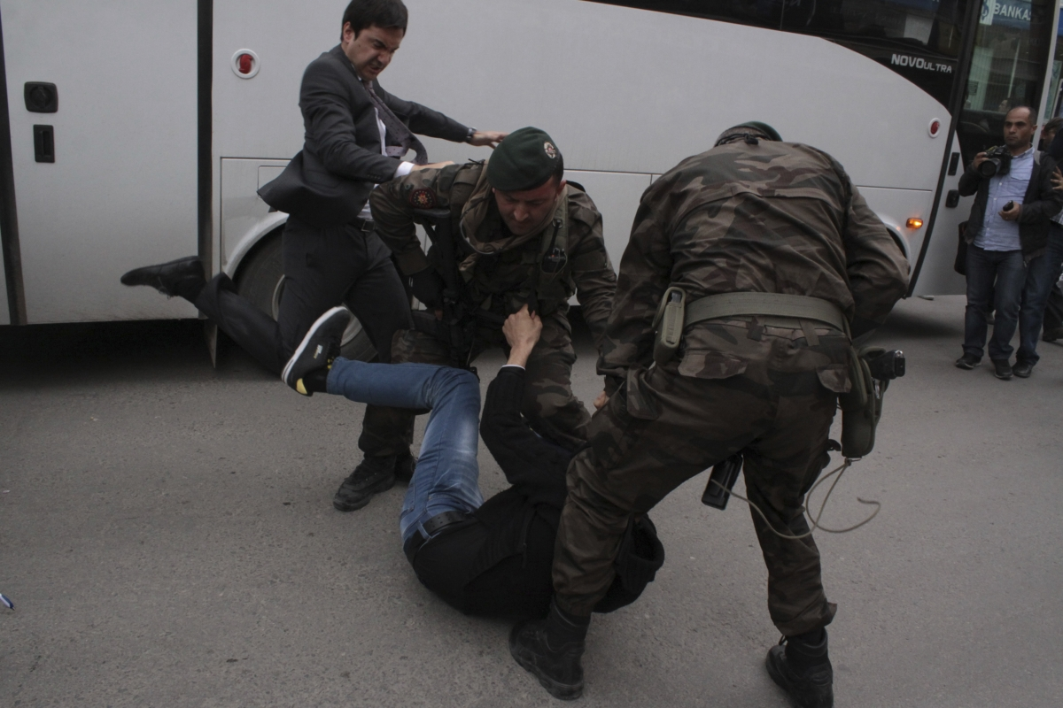 A protester is kicked by Yusuf Yerkel (L), advisor to Turkey's Prime Minister Tayyip Erdogan, as Special Forces police officers detain him during a protest against Erdogan's visit to Soma